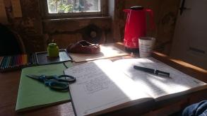 Schreibtisch mit Thermoskanne, Heften, Stiften