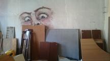 Möbelteile an eine Wand gelehnt, dahinter aufgemalte Augen